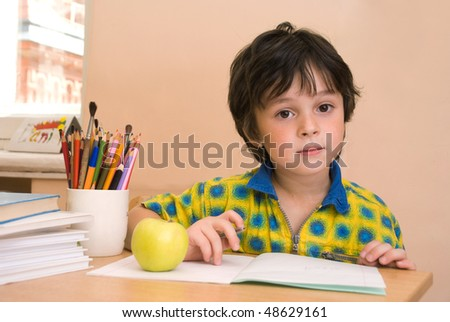 The boy with notebook and green apple and pencil in the classroom - stock photo