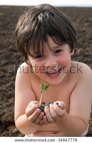 The boy with sapling on a black field - stock photo