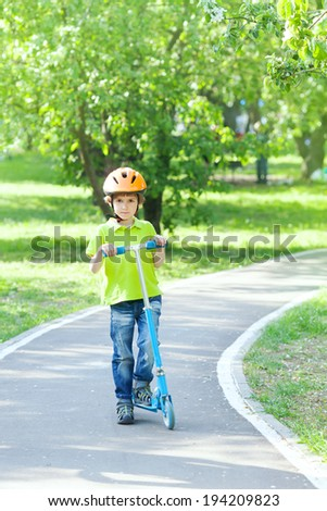 the boy with the scooter on the bike path in the Park - stock photo