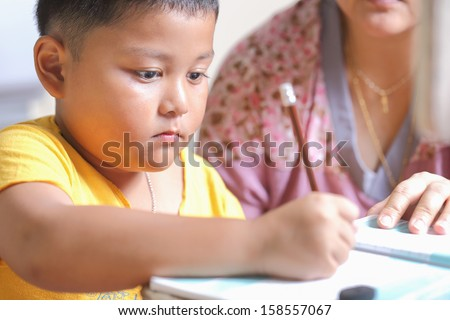 The boy work homework carefully - stock photo