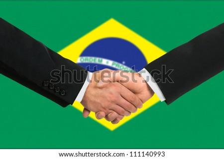 The Brazilian flag and business handshake - stock photo