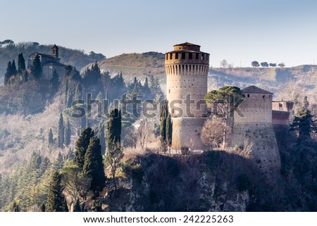 The brick walls of a medieval fortress and a sanctuary with belfry devoted to Blessed Virgin Mary on hills in the countryard - stock photo