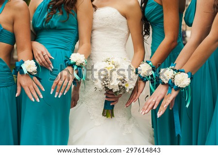 The bride and bridesmaids are showing beautiful flowers on their hands. - stock photo