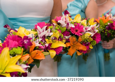 The bride and bridesmaids hold their colorful bridal flowers in a row. - stock photo