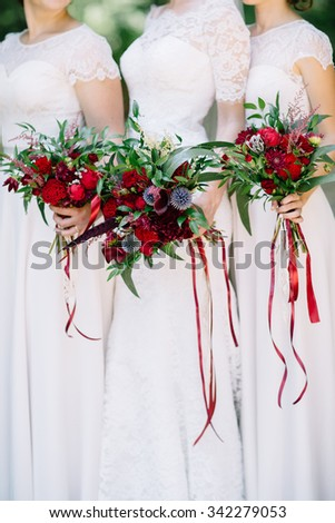The bride and bridesmaids wedding bouquet with red - stock photo