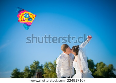 the bride and groom and a kite  - stock photo