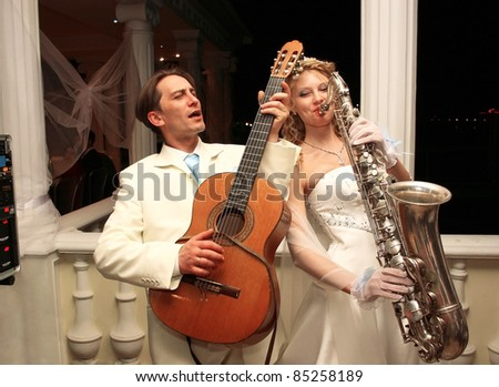 The bride and groom are entertained guests at a party in honor of their wedding - stock photo