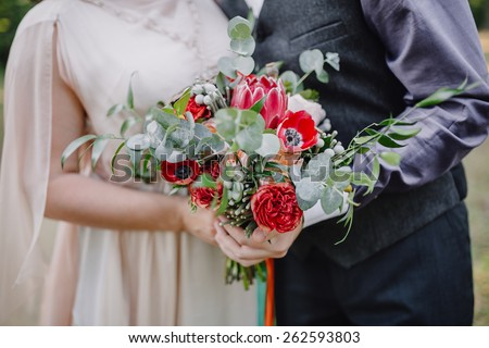 the bride and groom are holding a bouquet in the bohemian style - stock photo