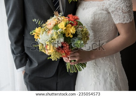 The bride and groom holding wedding bouquet of roses and love flower  - stock photo