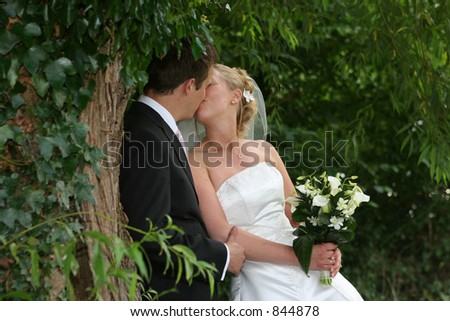 The bride and groom kiss after the wedding - stock photo