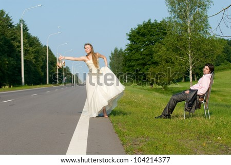 The bride and groom on road waiting for a car - stock photo