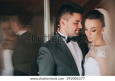the bride and groom on the balcony in the hotel room - stock photo
