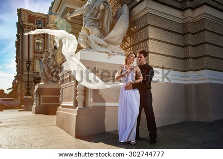 The bride and groom pose for a wedding photo shoot alongside a beautiful architecture - stock photo