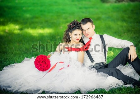 The bride and groom sit on the grass. - stock photo