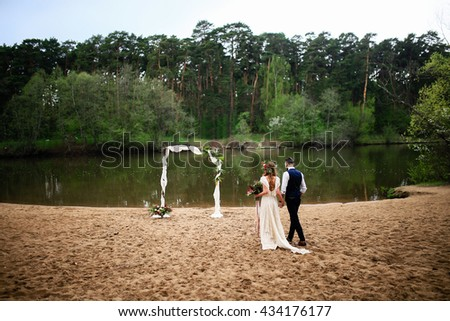 the bride and groom walk down the beach to the wedding arch - stock photo