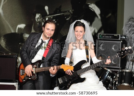 The bride and the groom with  guitars. - stock photo