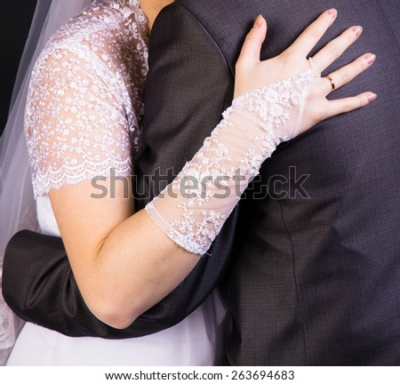 The bride hand on the back of the groom. Gentle loving hug - stock photo