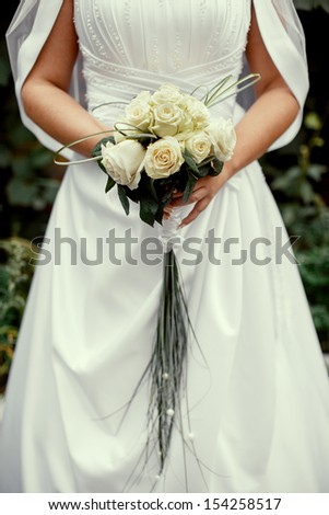 the bride holds a wedding bouquet from white roses - stock photo