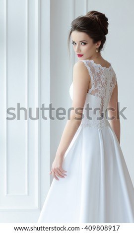 The bride in a magnificent white dress stands back and looks over his shoulder. - stock photo