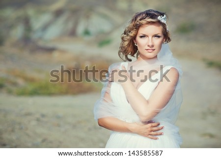 The bride in a wedding dress in the middle of the desert - stock photo