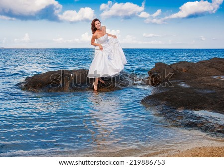 The bride in a wedding dress on a rock in the sea on a background of clouds - stock photo
