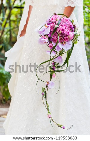 The bride in her wedding dress with her beautiful bouquet filled with pink roses and orchids. - stock photo