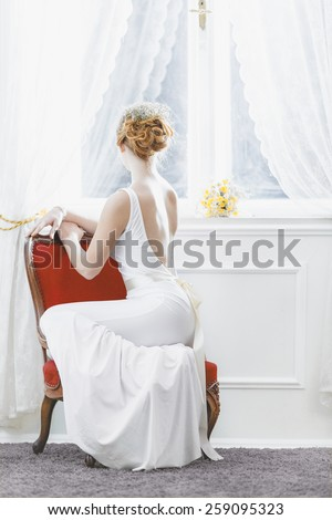 The Bride / Young women with wedding dress in very bright room, some fine film noise effect added - stock photo