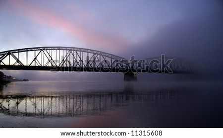 The bridge in foggy sunrise with reflection in water - stock photo
