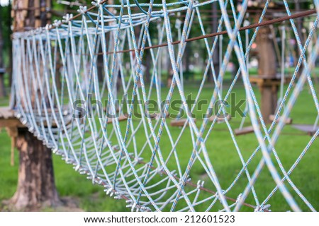 The bridge of logs tied to the ropes, part of a ropes course - stock photo