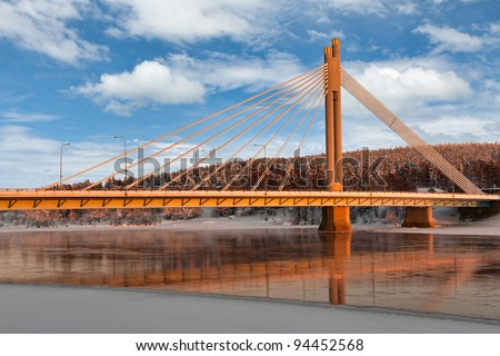 The bridge over the river against the backdrop of winter snow-covered forest - stock photo