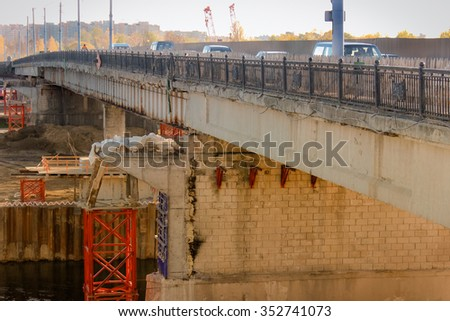 The bridge over the river repair. Repair of the bridge on which the moving machine. Side view of the bridge. - stock photo