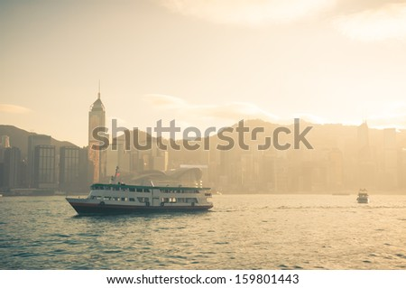 The bright afternoon sunlight beams across Victoria Harbor in Hong Kong. - stock photo