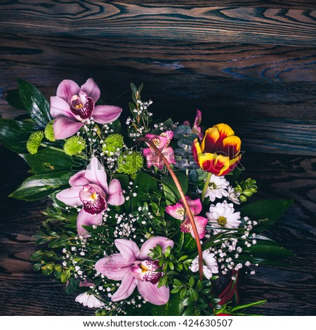 the bright bouquet of flowers. Pink orchids. Wood texture - stock photo