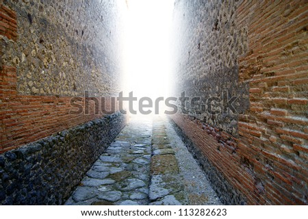 The bright light in the distance between the old brick wall - stock photo