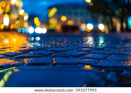 The bright lights of the evening city after rain, headlights of the cars riding straight. View from the pavement level next to the roadside puddle - stock photo