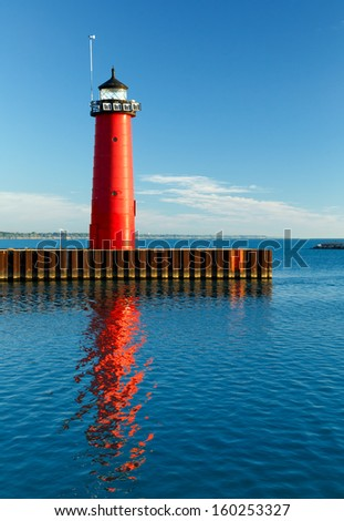 The bright red Pierhead Lighthouse at Kenosha, Wisconsin is reflected in early morning light on the waters of Lake Michigan. - stock photo