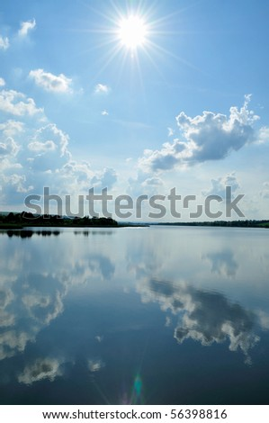 The bright sun with the clouds reflected in water - stock photo