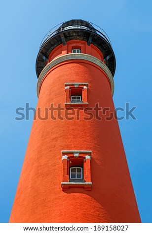 The brilliant red Ponce de Leon Inlet Lighthouse, south of Daytona Beach, Florida, is viewed from below looking up. - stock photo