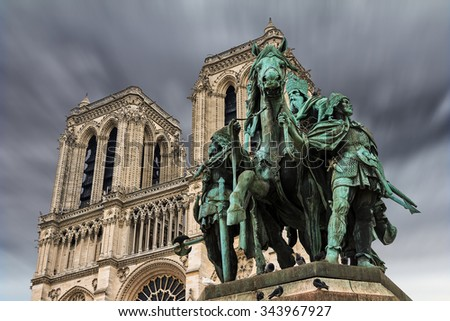 The bronze equestrian statue Charlemagne et ses Leudes (Charlemagne and his guards) in front of Notre Dame Cathedral with an ominous sky - stock photo