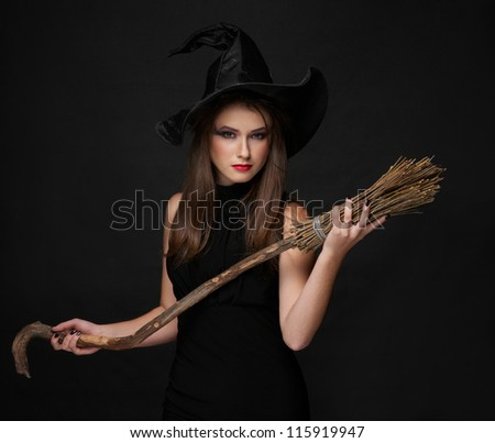 The  brunette witch with a broom in a black dress in the studio - stock photo
