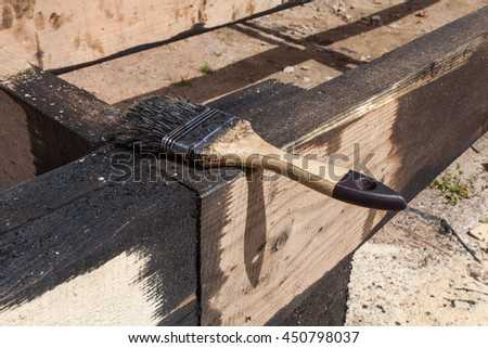 The brush for painting black coal tar or bitumen at  surface  of terrace for waterproofing during the building renovation - stock photo