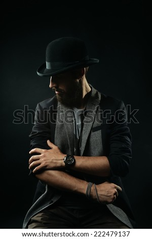The brutal bearded man in a black bowler hat rolls up sleeves of his jacket - stock photo
