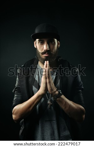 The brutal bearded man in a black fitted hat praying - stock photo