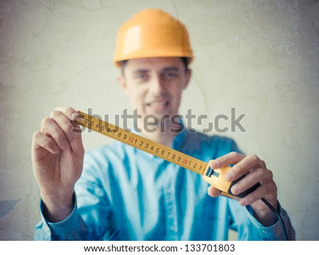 The builder in a helmet with a meter - stock photo