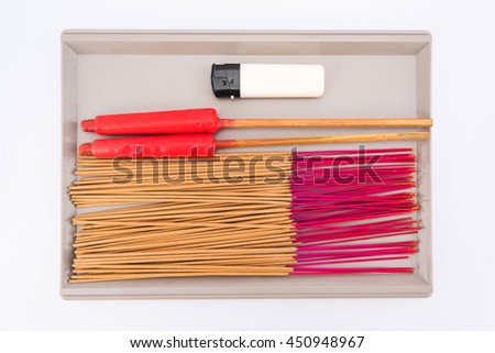 The bunch of incense sticks, two red candle ceremony Chinese candles and a lighter. Incense use in religious ritual popular in Asia. It's burned to intend as a sacrificial offering to various - stock photo