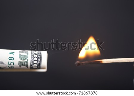 The burning match sets fire to dollar - stock photo