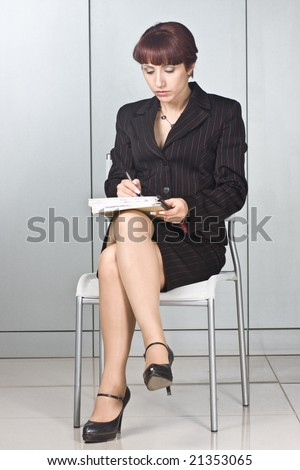 The business woman with a pen in hands sits on a chair at office - stock photo