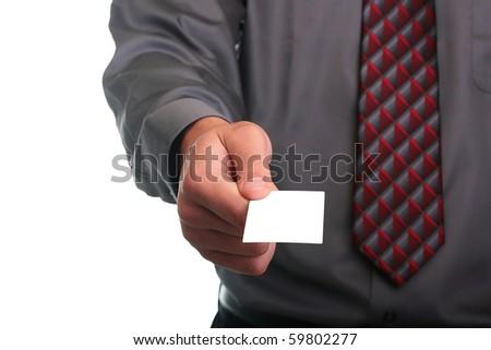 The businessman in a grey shirt and a tie stretches out a business card. - stock photo