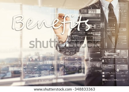 the businessman in the office is writing on the transparent board: Benefits - stock photo