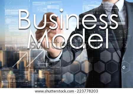 the businessman is writing Business Model on the transparent board with some diagrams and infocharts with the city in the background  - stock photo